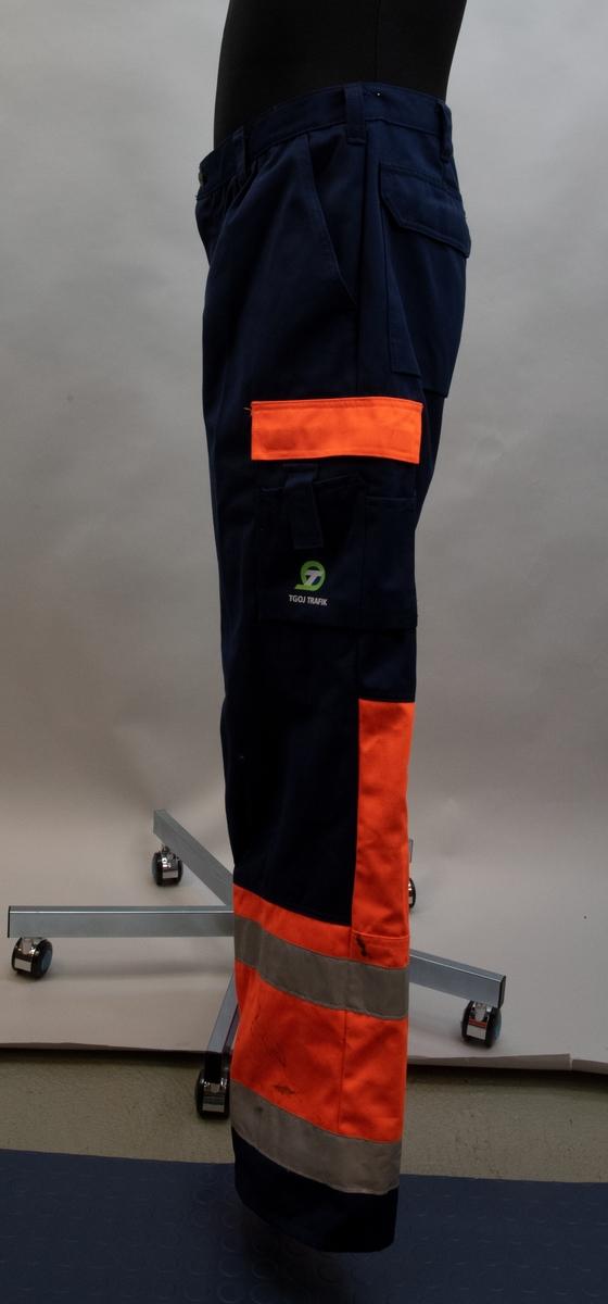 Varselbyxa av blått tyg med två rader av silverfärgade reflexband på byxbenen och avvikande partier i flourescerande orange tyg. Byxan räknas in i skyddskläder med god synbarhet klass 1. Svart plastring vid högra fickan för fastsättning av exempelvis nyckelknippa.
