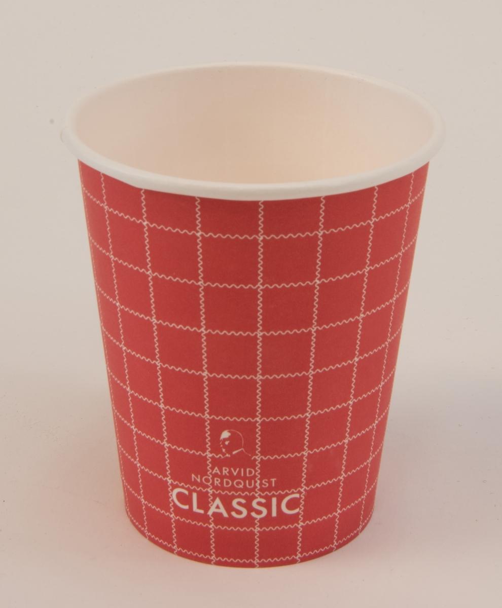 """Pappersmugg för engångsbruk (:1), utvändigt röd med vitt rutmönster, med löstagbart vitt plastlock (:2). De vita ränderna som bildar rutmönstret är vågiga. På muggens ena sida står det """"SJ BISTRO"""" och på andra sidan reklam för kaffemärket Arvid Nordquist Classic. På plastlocket finns tre stycken runda välvda """"knappar"""" som går att aktivera för att ange om kaffet är koffeinfritt (decaf), innehåller mjölk eller grädde (cream) eller är svart (black). På locket finns även tillverkarens namn """"Tingstad""""."""