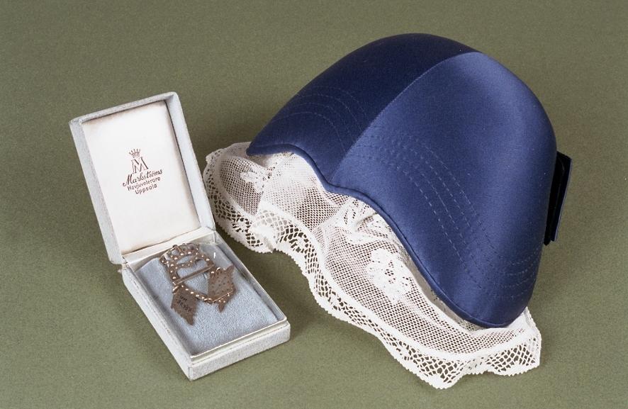 Upplandsdräkt: klänning i blårutigt bomullstyg, förkläde och schalett (UM30957a), blå hätta med tyll (UM30957b), silverbrosch från Markströms (UM30957c) i ask (UM30957d).