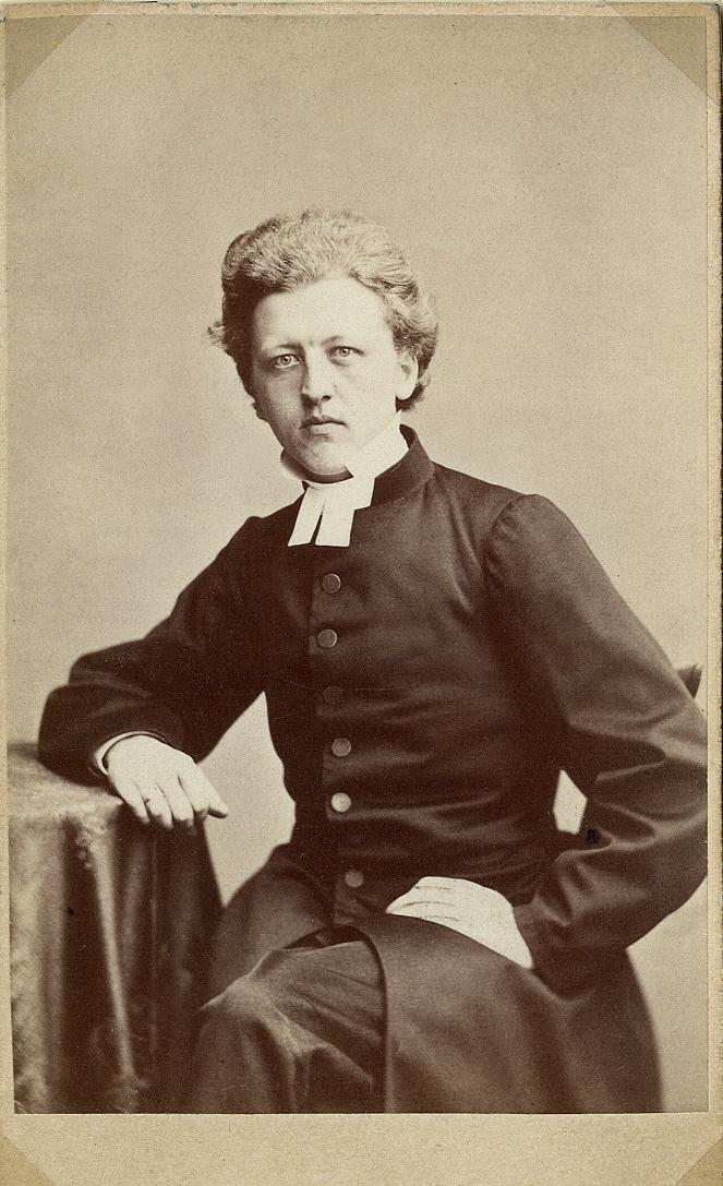 Foto av en man i prästrock och prästkrage, Han sitter vid ett bord med en lång duk.  Knäbild, halvprofil. Ateljéfoto.
