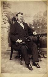 Foto av en man i bonjour med väst och fluga. Han sitter på e