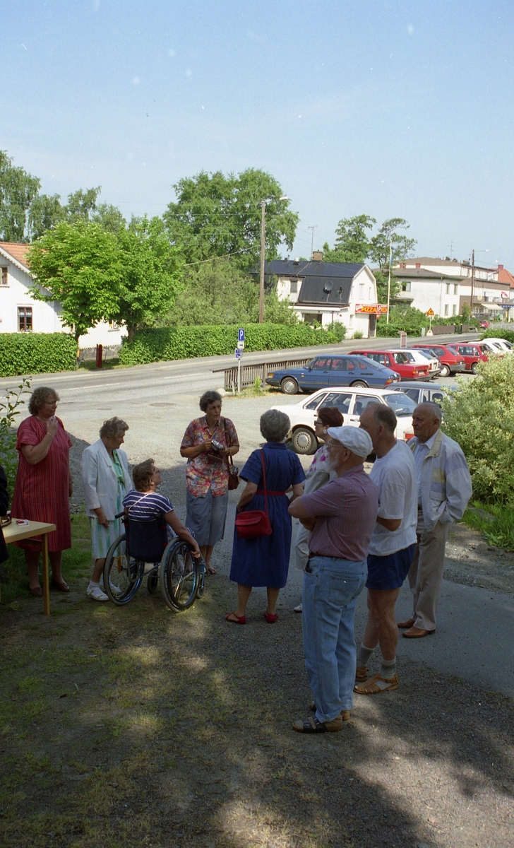 """Invigning av Ekebackens Hantverksgård (tidigare John Lindströms möbelsnickeri) på Gamla Riksvägen 81, början av 1990-talet. Besökare står samlade utanför på grusvägen. I bakgrunden till vänster ses 1. """"Hagen"""" Vommedal Östergård, 2. Kafé Brittbo och 3. Petershof."""
