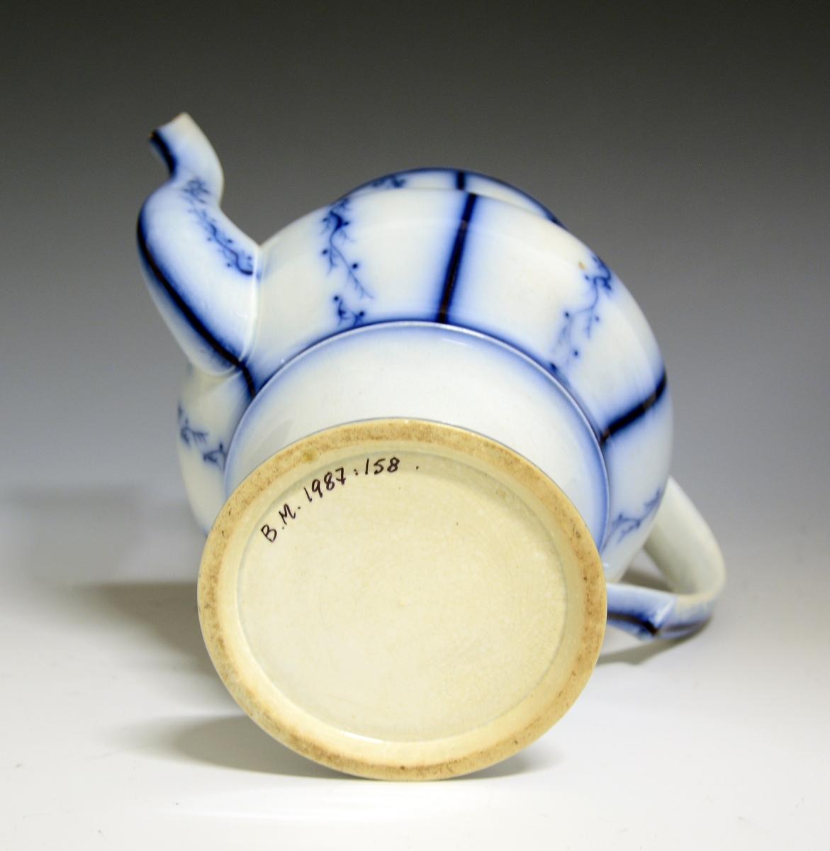 Prot: Kaffekanne med blå strek- og bølge-dekor. Hanken er C-formet. Tuten er noe skadet. Gjenstanden bærer ikke noe firma/fabrikkmerke.