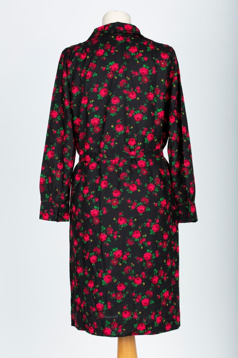 A: Kjole Skjorteblusekjole. Lange ermer med mansjett, rødt og grønt rosemønster på sort bunn. Stolpeknapping i halsen, Brystsnitt. rette sider.   B: Knyttebelte  Kjolen sydd av mor, Ella Viktoria Hagen.