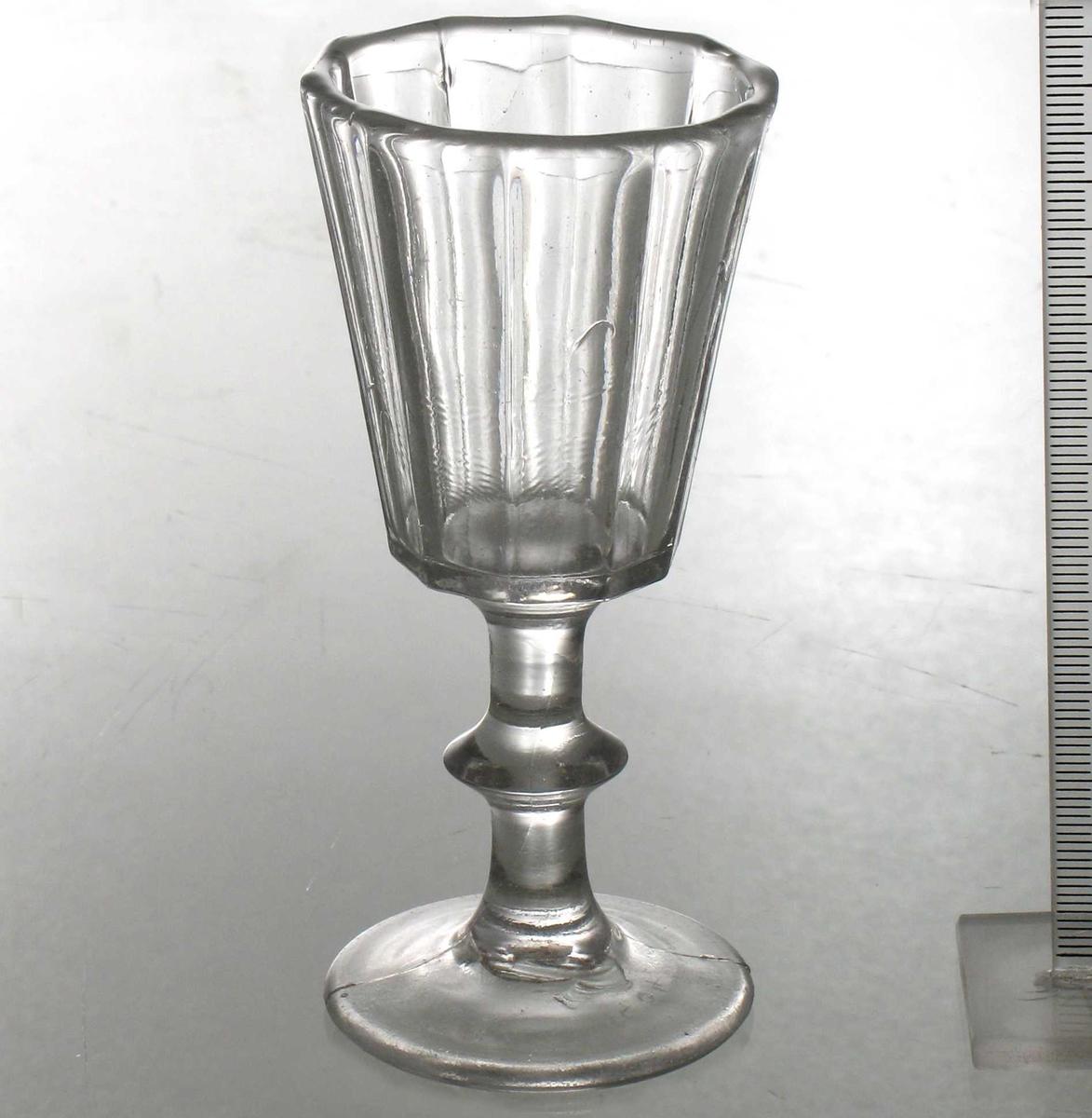 Pressglass. Rund glatt fot med støperand tvers over.  Rund stett med en baluster pm. Kantet  beger med skrå, rette sider.