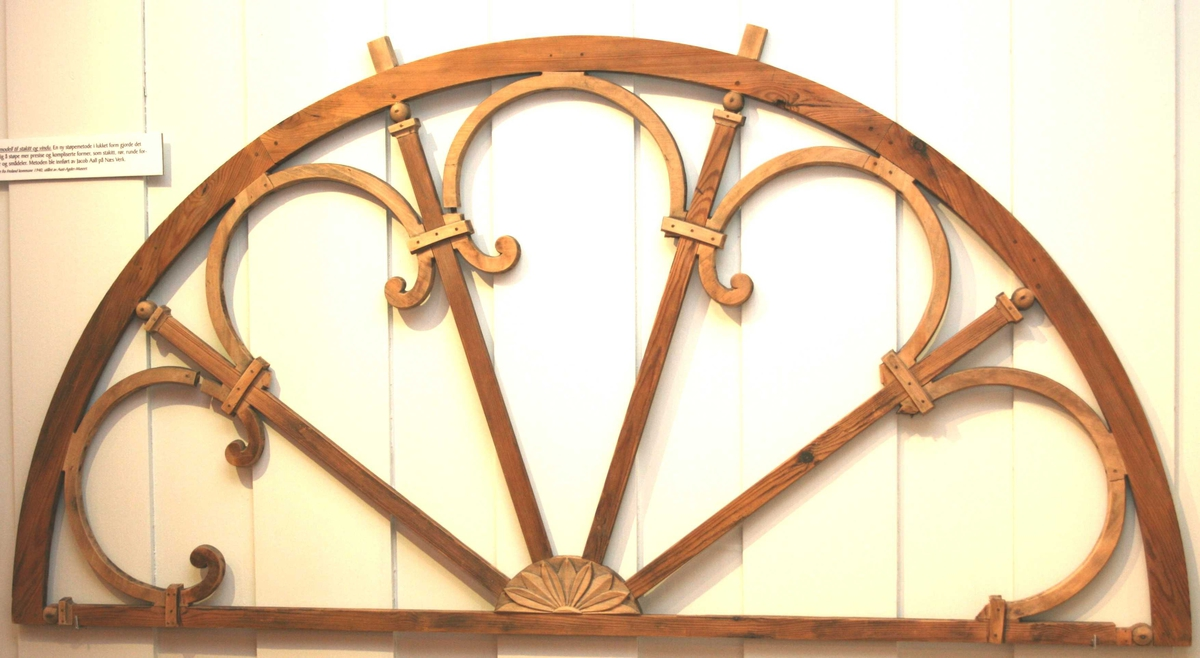Støpemodell til vindu  eller pørtaloverstykke  halvsirkelformet   Furu, umalt.  4 radiære sprosser. i hvert felt øverst  mot buen en halvsirkelformet bue som ender  i volutt. Npm. palmettmotiv halvsirkelformet.  Tilstand: volutter i den ene bue mangler.