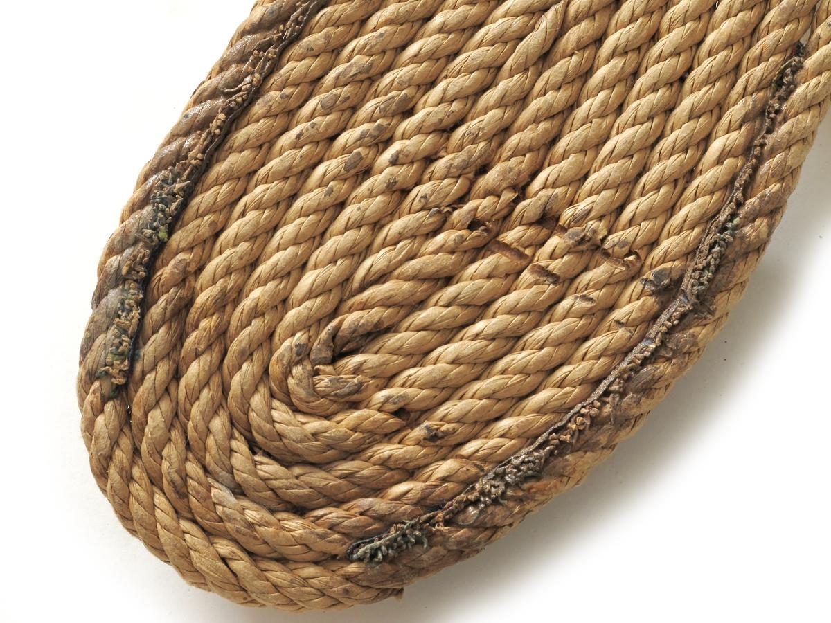 Sandaler,  fra krigen 1940-1945. Såle av papirtau, innlegg av papirstrie, helkappe   og forstykke av papirstrie i naturfarget med blå bånd. Celluloselim og trådstift. Størrelse 38. L.såle 26.