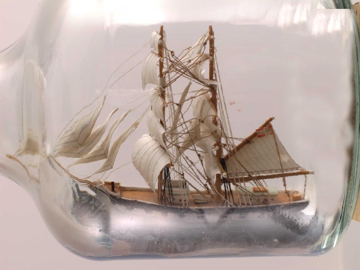"""Brigg """"Ternen"""" , med grått skrog og kanonporter malt i sort og hvitt , fulle seil. Lys blå småbølget sjø."""