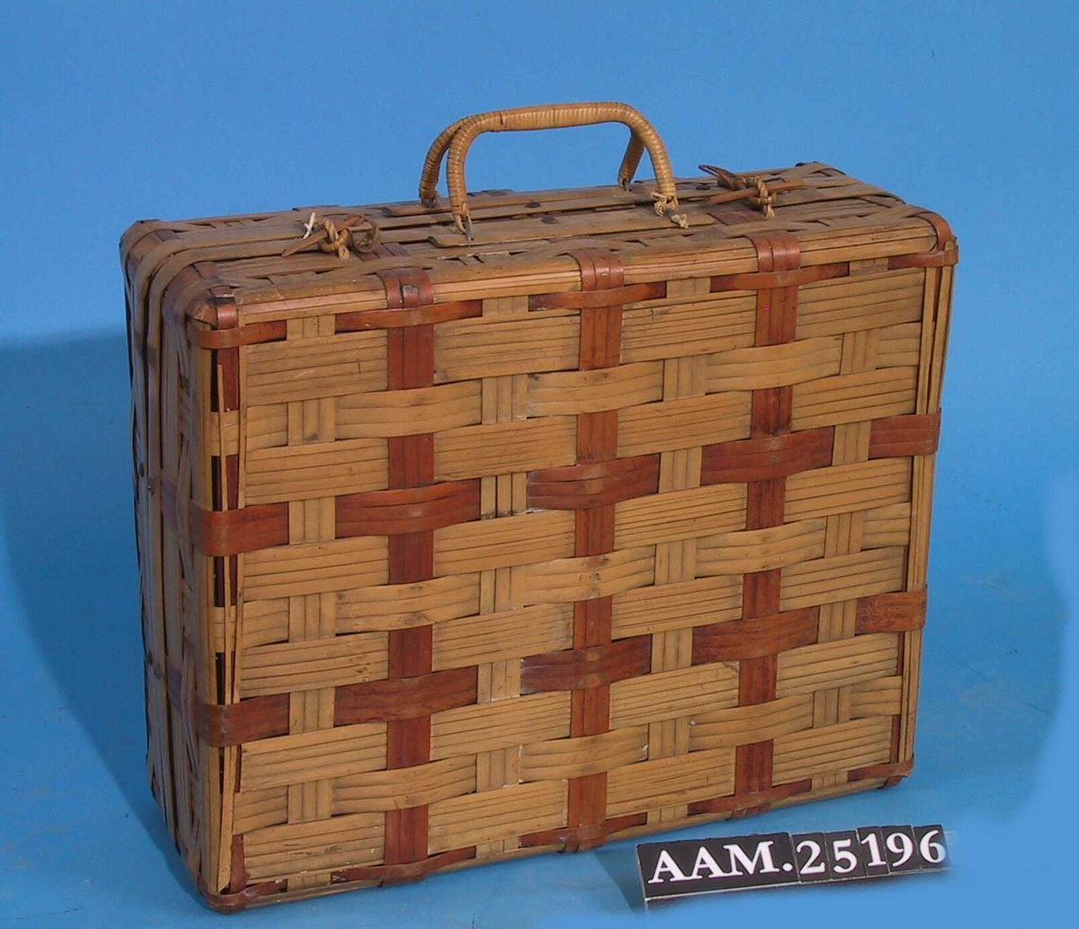 Koffert av bambus. Flettet av splittet bambus av bredder varierende mellom 0.3 cm til 2.3 cm. Bambusen er av to farger som danner mønster.  Avlangt, rett avsluttet på to sider. Skådd kant.