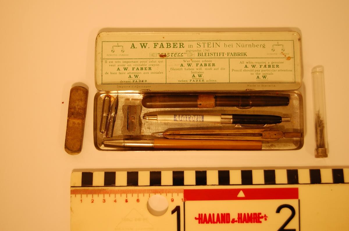 Metalletui med lokk.  Inneholder tørrblekkpenn, to pennesplitter, Hylse med bly, blyant, passer, viskelær, blyantspisser, glassrør med knappenåler.