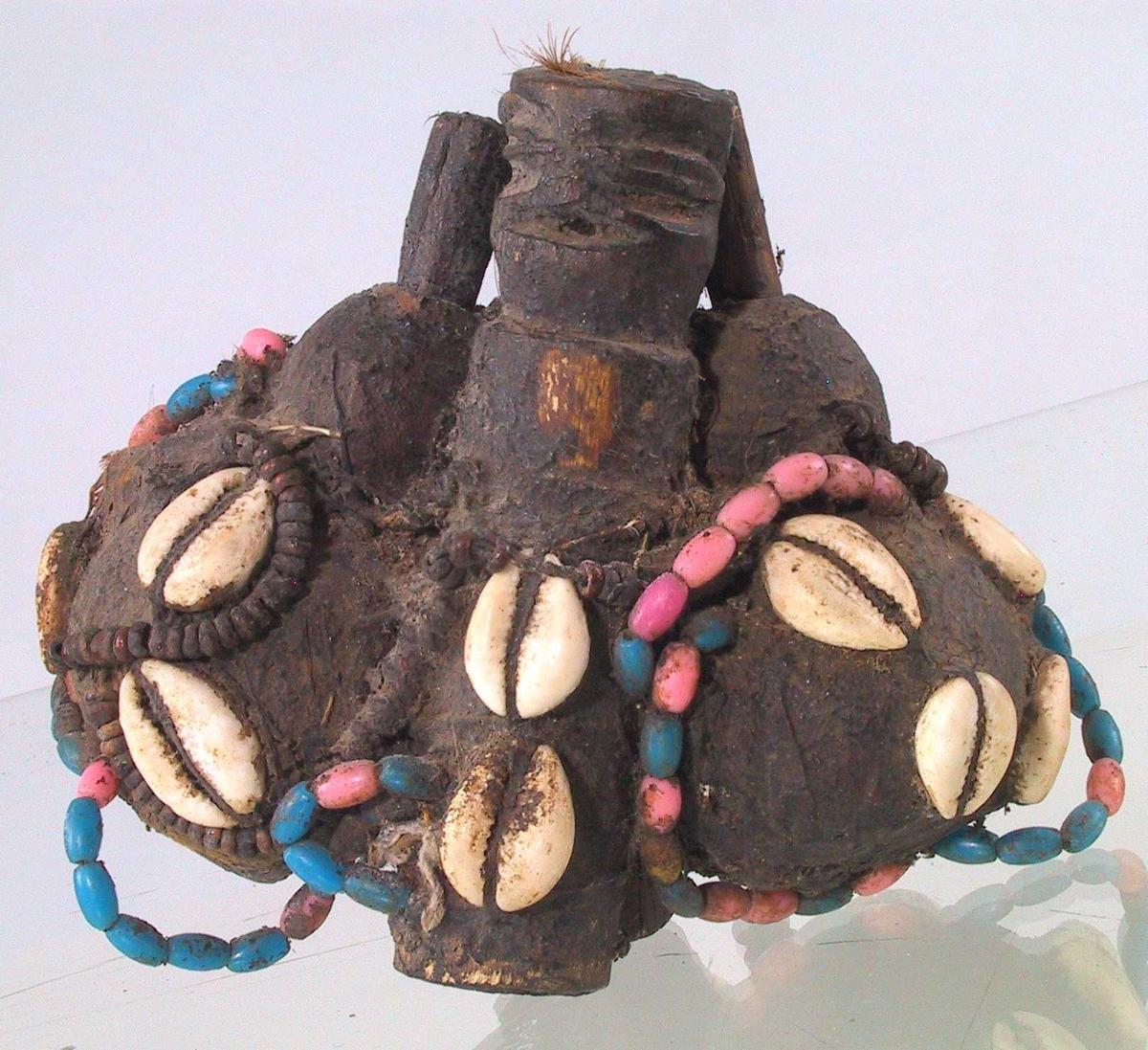 To minitrommer, to små kalebaser, bundet sammen, pyntet med kauriskjell, perler, fjær, m.m. Fyllt med fint grått pulver, trolig aske.
