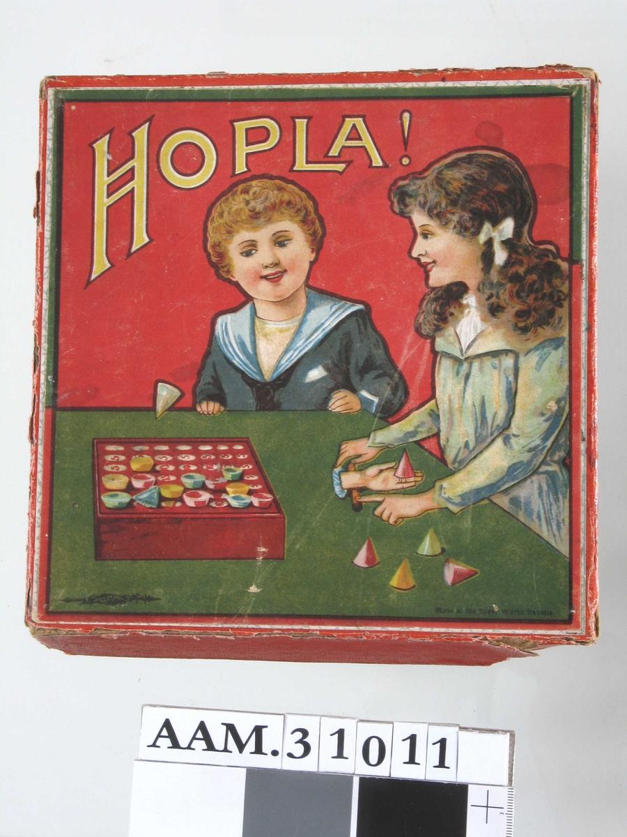 På eske: Jente og gutt ved et bord, leker med et Hopla-spill.