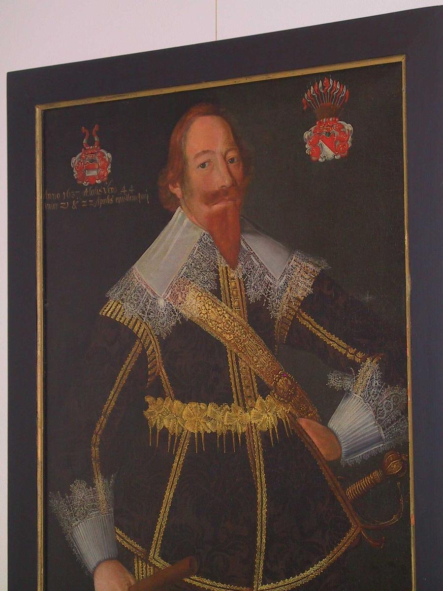 Portrett av Erik Krabbe  f. 21 april 1593, d. i Tønsberg 26 nov: 1659, sønn av  Christen Krabbe til Bjørholm og Lisbet Høg.  G. m. Maren Mogensd. Kruse.  Knestykke,  venstrevendt,   yngre mann m. rødt hår og skjegg,  i brun drakt m. mørkebrunt mønster og gullsøm, flat   kniplingskrave.  V. hånd i hoften, h. ned langs siden, griper om   marskalkstav.  Bakgr. mørkt gråbrun .  Øv. v. hj. fedr. våp: Krabbe: rødt skjold delt hor.  på midten av bred hvit bjelke.  Vedderhorn på hjelmen tilsvarende tverrstripet rødt, hvitt, rødt.  Øv. h. hj. mødr. våp: Høg: diagonaldelt skjold,  nedre del hvit, øv. rød.  13 faner, hvite og røde, på hjelm,  Innskr. under   Krabbevåpenet:   Anno 1637, statis Vero 44, Inter 21 & 22 Aprilis ejusdem Anni.
