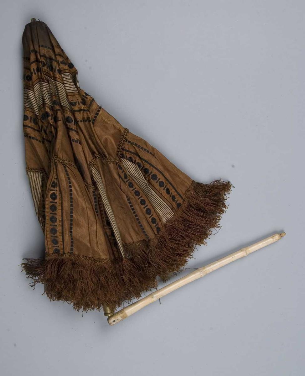 Liten brunmønstret parasoll med frynser langs kanten. Metall- og trespiler. Stangen er leddet og låses med en messingholk, malt hvit. Den nederst delen av stangen ser ut som bambus. Håndtak mangler.