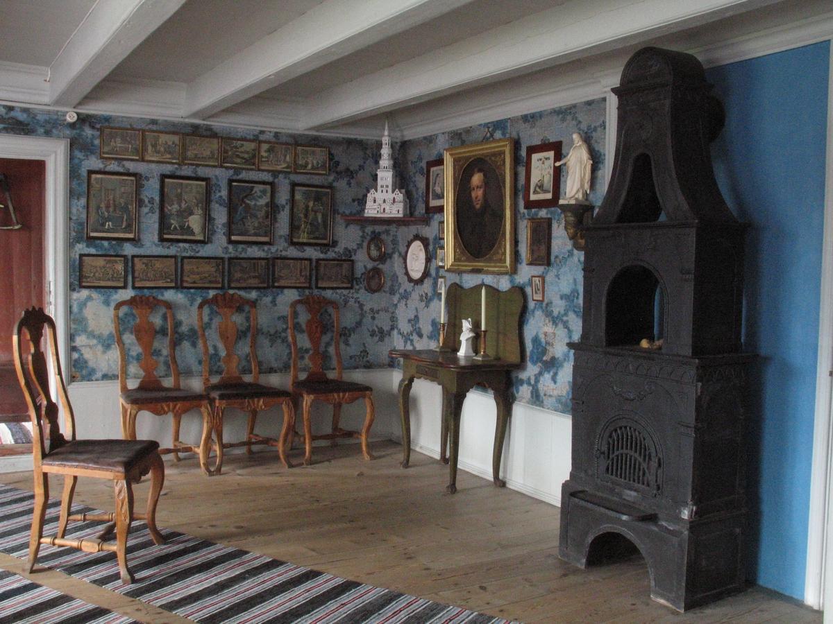 Merdøgaard. Interiør storstua. Jernovn, bilder på veggen, stoler, velurtapet, brystpanel.