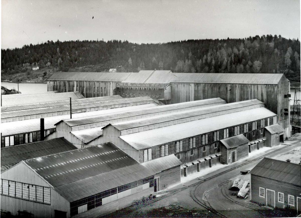 Nitriden. Oversiktsbilde. Nærmest: Pakkeri, videre ovnshusene og omformerstasjonen. Tromøysund. Tromøy i bakgrunnen. Trallebane og smie til høyre.