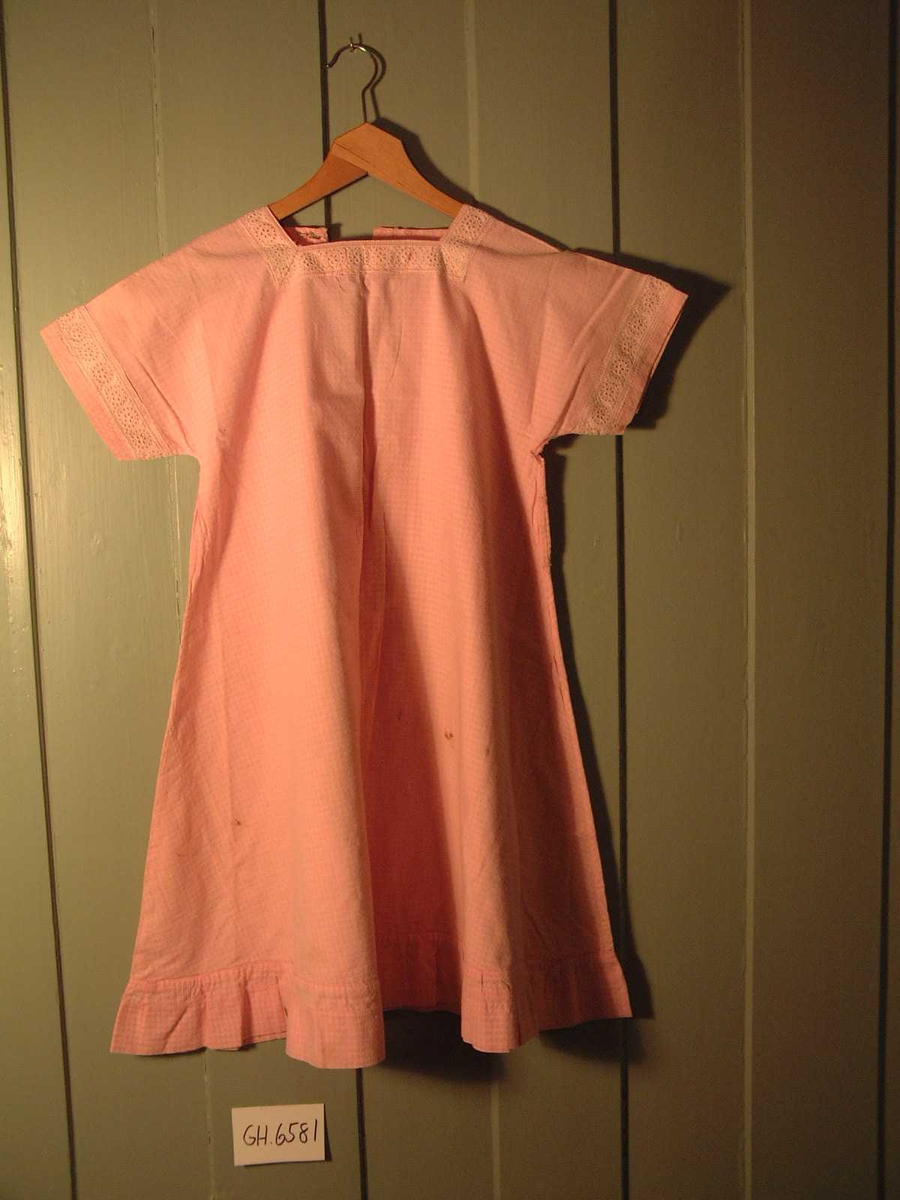 Kjole bomullsstoff,  ruteeffekt og mønsterveving. Korte ermer og påsydd kappe nederst. Ferdigkjøpt  pyntebånd nederst på ermene og i hals. Beltestropper i hver side.