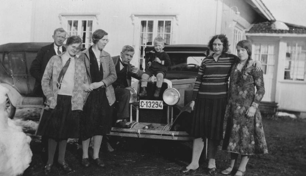 Gruppebilde, 7 personer foran en bil.