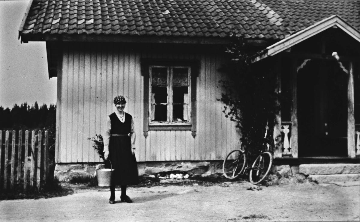 Kvinne, melkebøtte, bolighus, sykkel
