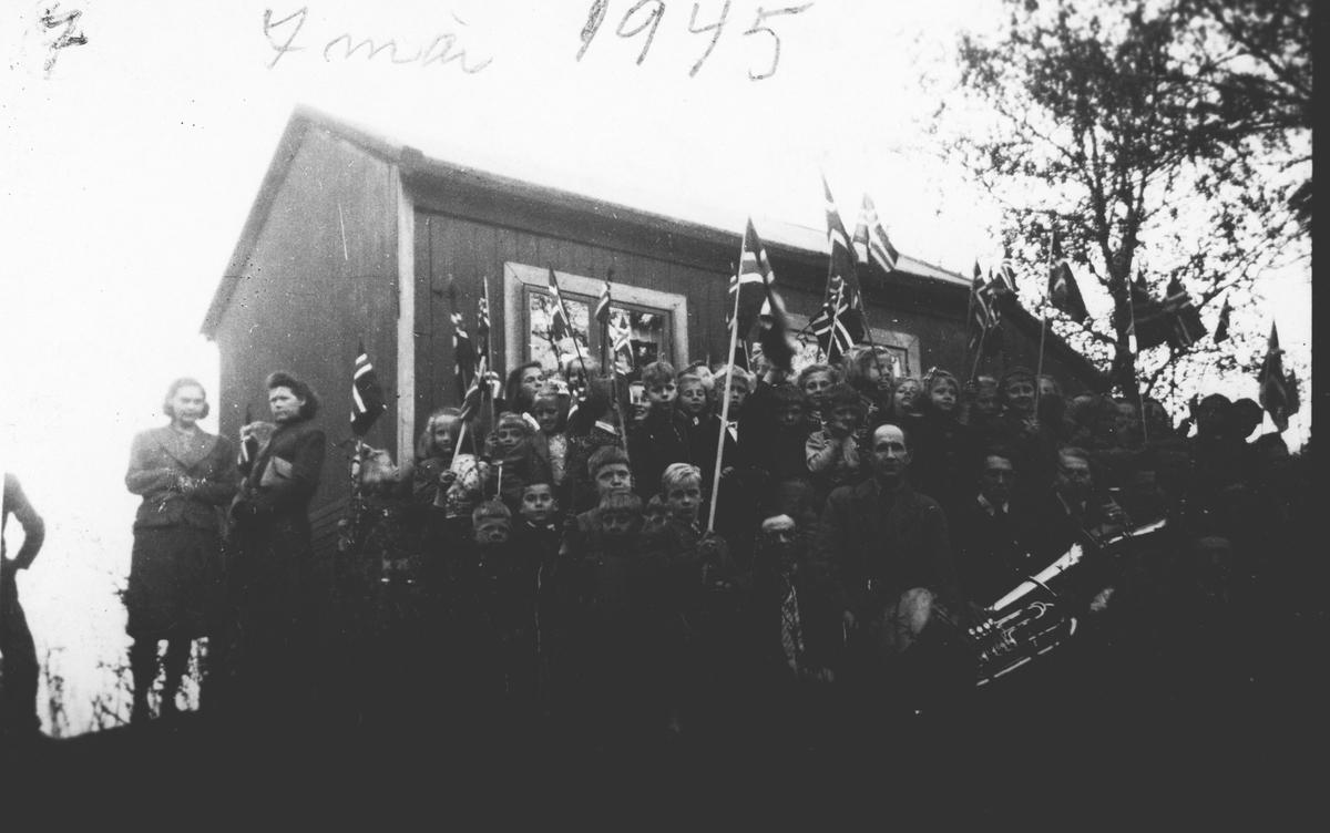 Musikk-korps oppstilt foran hytte.