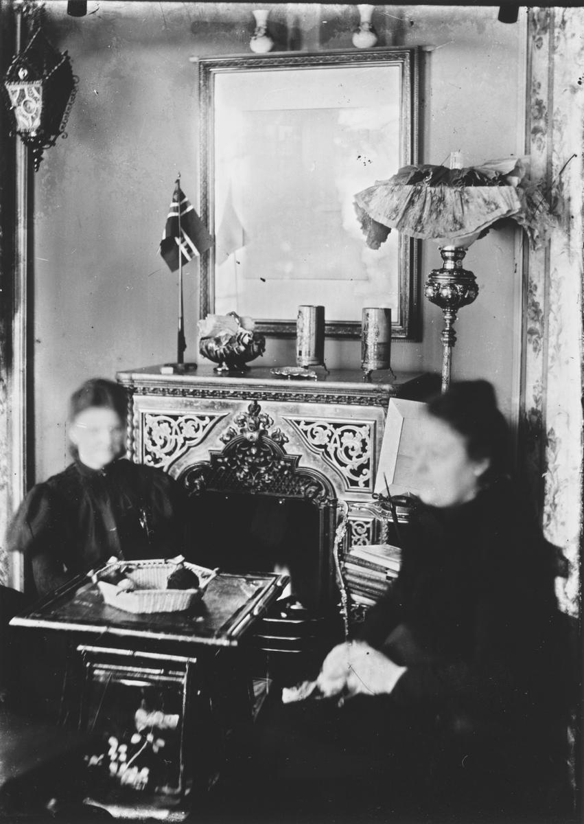 Kvinner med håndarbeide foran peisen.
