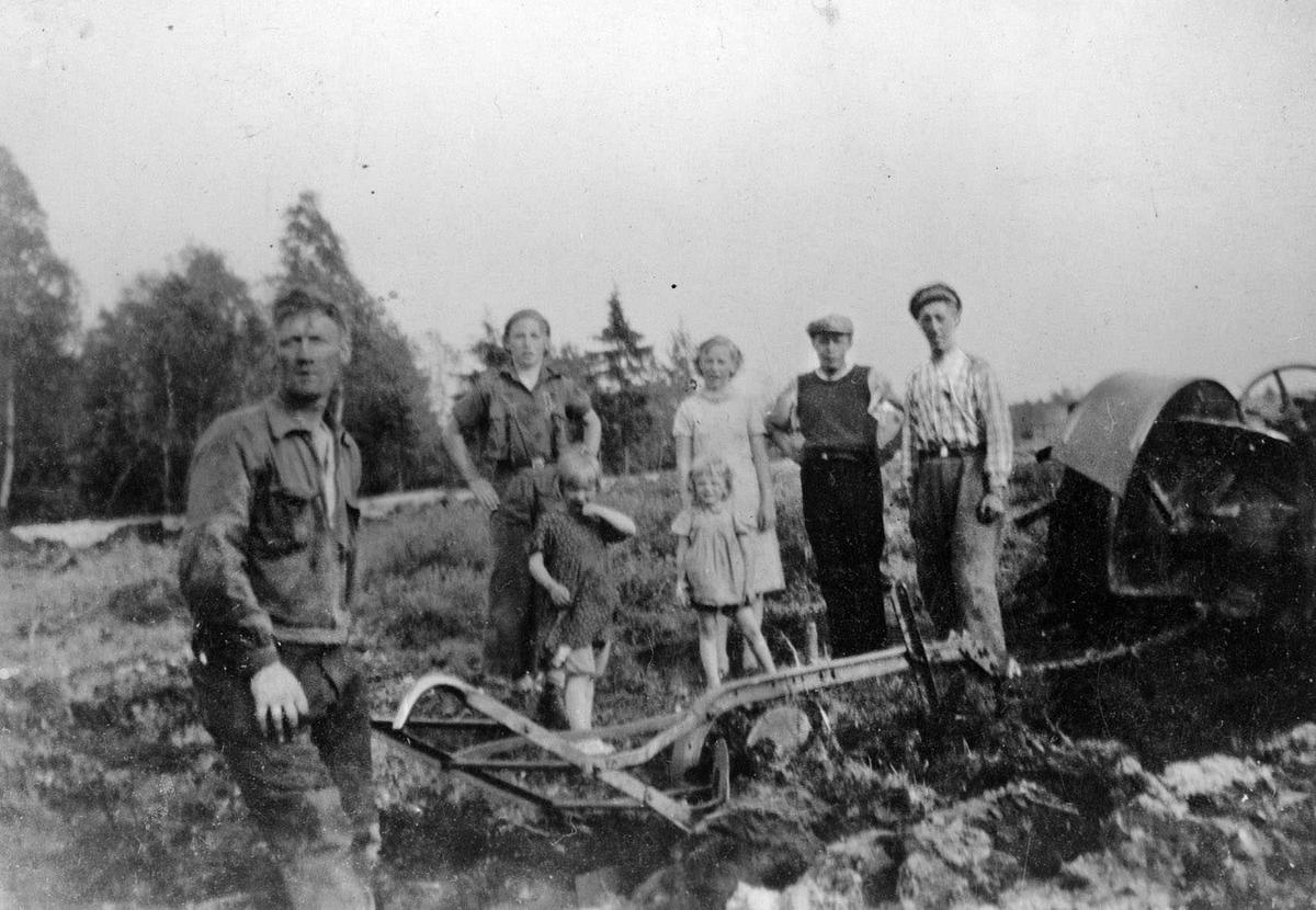 Gustav Lange med plogenetter traktoren. Lengst til høyre broren Odd. Kvinner, barn og arbeidskarer seg på.