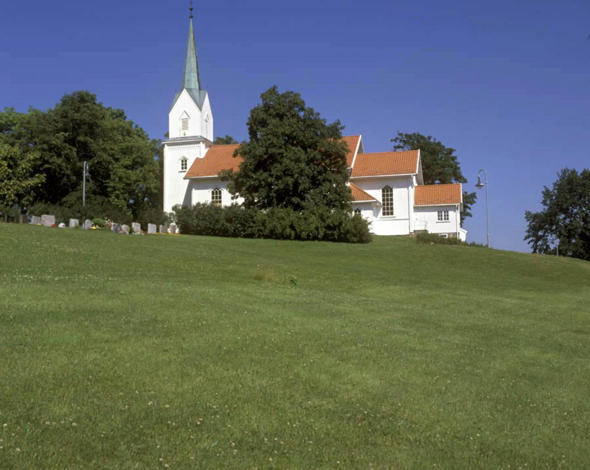 Rælingen kirke, lengderetning, gravplass i bildets høyre side, gressplen i forgrunnen.