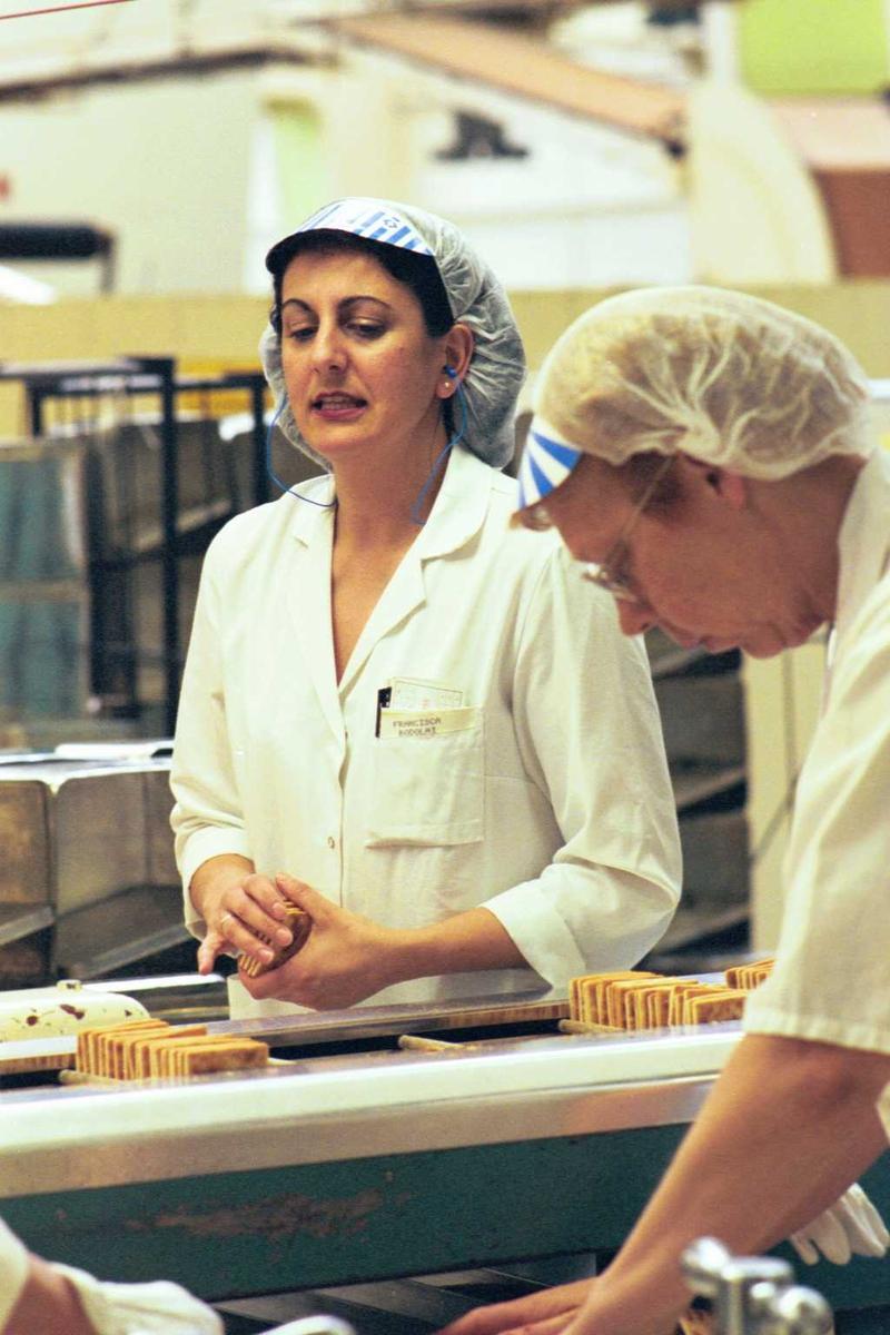 Cream Cracker, kjeks, maskiner, arbeidere, arbeidstøy, kvinner, fabrikkmiljø. Et halvt pakkelag ved A-linja
