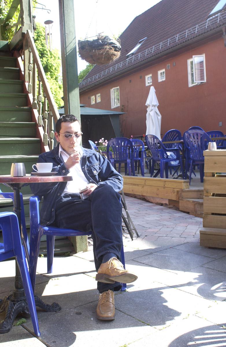 Pubgjest sitter ved et bord med røyk og kaffe i bakgården Milde Moses Pub & Spiseri i Drøbak