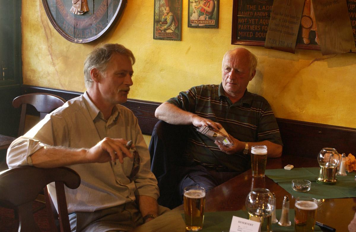 2 menn ved et bord med sigar og tobakkspung. Bowler & Spisepub.