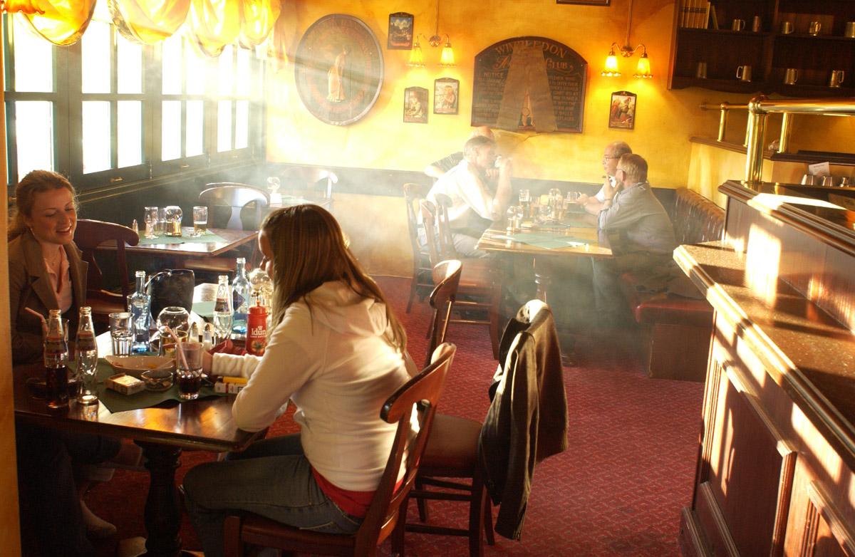 Røykfylt rom. 3 jenter ved et bord i forgrunnen. Bak 4 menn ved et bord med sigarer og pipe. Bowler & Spisepub.
