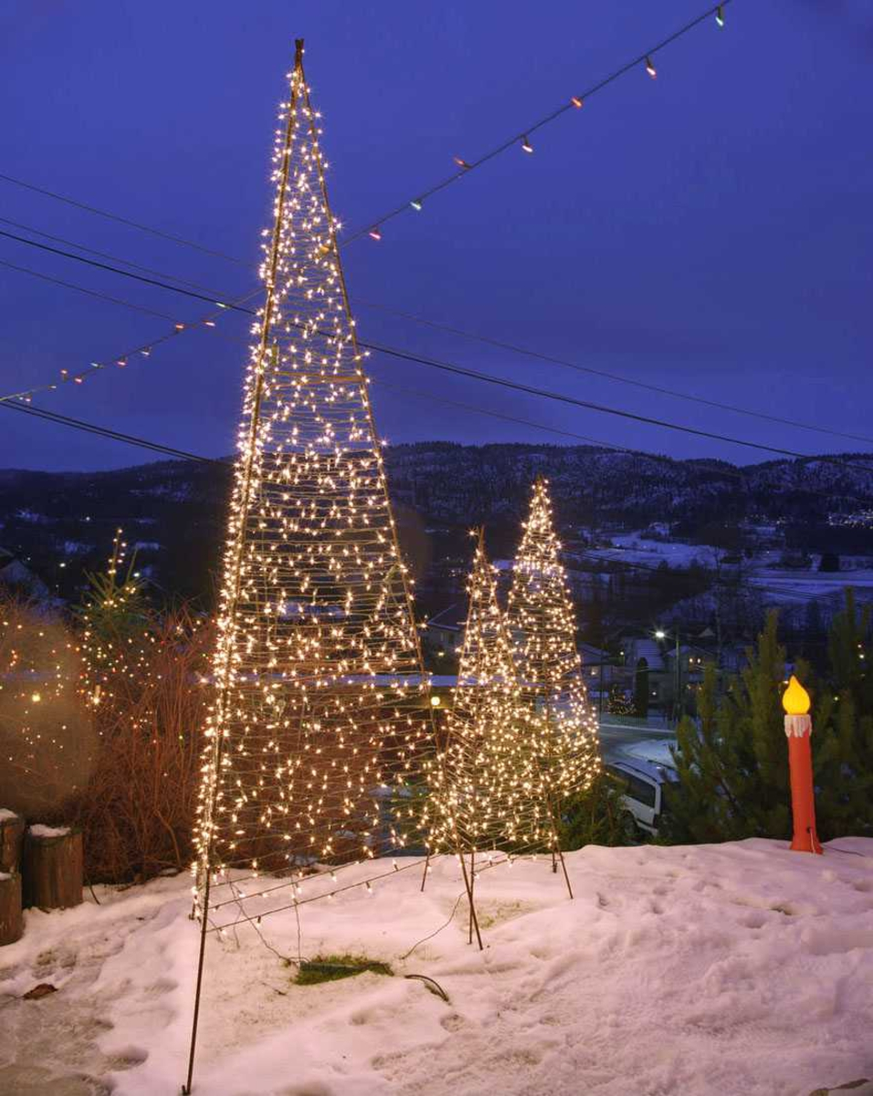 Julebelysning  Fantastisk julebelysning på enebolig. Lysende hvite pyramider i hage.