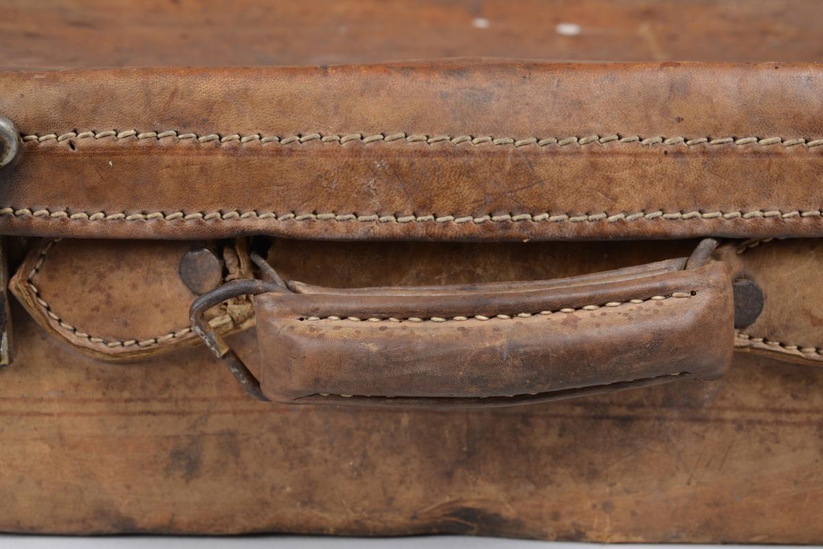 Rektangulær koffert i lysebrunt skinn med metall-låser og et håndtak i polstret lær med metallfeste. Metallforsterkninger i hjørnene er festet med bolter. De lyse sømmene langs lokket er brukt som dekorativt element, langs hver side på kofferten er det innpreget enkle linjer. 4 metallknotter er monterte på undersiden av kofferten for stabilitet og styrke. Kjernen er av papp. Innsidene er fòret med naturhvit bommullslerret. En rektangulær lomme befinner seg på innsiden av lokket. Lokket holdes oppe i åpen tilstand ved hjelp av reimer på hver side. Reimene er trukket med samme lerret som fòret.