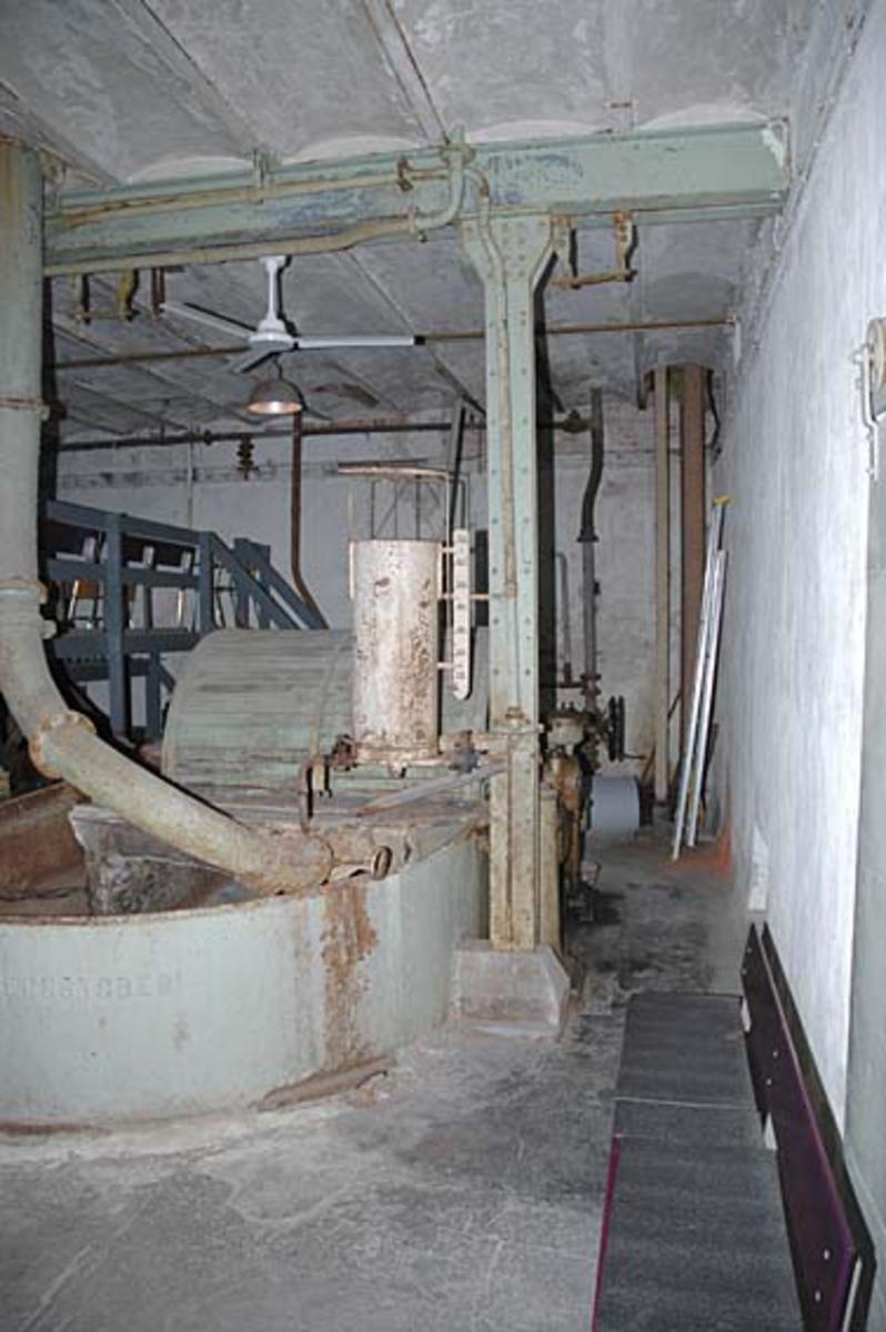 Interiør fra Klevfos Cellulose- & Papirfabrik i Løten i Hedmark.  Fabrikken med tilstøtende bebyggelse har siden 1986 vært drevet som Klevfos industrimuseum.  Dette fotografiet er fra hollenderiet, som ligger i en teglmurt bygning med etasjeskiller utført som kappehvelv av tegl mellom stålskinner.  Fotografiet viser hvordan kappehvelvene bæres av klinknaglete H-bjelker av stål.  I forgrunnen på dette fotografiet ser vi en av hollenderne.  Det dreier seg om et digert kar med en innvendig midtvegg, samt en valse (såkalt «kubbe») og et «grunnverk».  Ytterflatene på de roterende hollenderkubbene var besatt med skinner eller «kniver» av stål eller fosforbronse.  Disse maler mot det faststående grunnverket, som også har kniver av samme materiale.  Malingsgraden (fibrilldannelsen) hadde stor betydning for papirkvaliteten. Kubben var overbygd med et tredeksel, der et par manglende bord gav muligheter for et visst innsyn.  Hollenderen på dette fotografiet ble levert fra Drammens jernstøperi i 1910, da Klevfos-fabrikken var under gjenoppbygging etter en storbrann året før.   I bakgrunnen på dette fotografiet ser vi et lite oppbygg med stålrørsmøbler.  Dette er sitteplasser for publikum under forestillingen «Arbesdaer», som siden premieren i 1988 har vært oppført 5-6 ganger hver sesong nettopp i fabrikkens hollenderi.  I en av visetekstene heter det blant annet:  «Og massa den må malas, malas i en kum. Vi har ti farge, har ti lim, Hollenderi, hollendera, det er vår arbeidsplass.» Ådalsbruk.