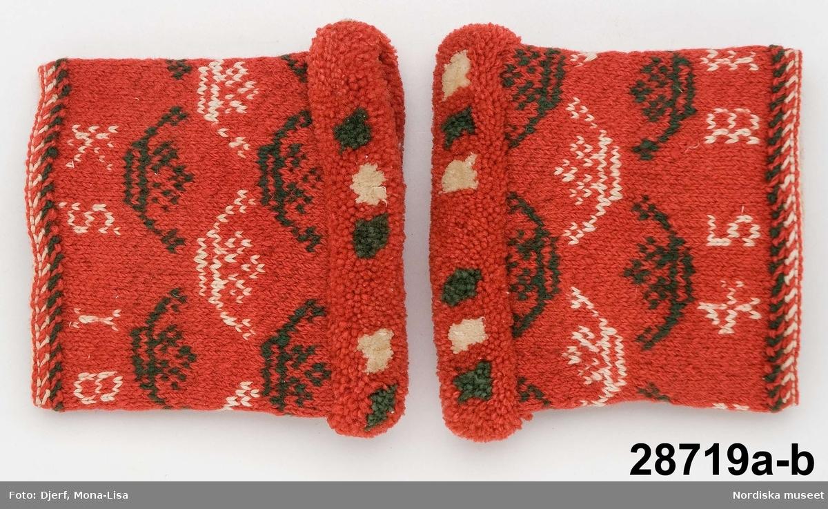 """a-b Ett par ärmmuddar, mönsterstickade med kronor i vitt bomullsgarn och grönt ullgarn på röd botten, instickad märkning i övre kanten BIKS 1845. Uppläggningskant i de tre färgerna. Flossabräm i samma färger med tätt knutna nockor på en vävd linnebotten, som klippts till en jämn valk och sytts fast på mudden.  Huvudliggaren: """"Till hört bonden Isak Karlsson, som fick dem vid 28 års ålder.""""  Stickade som gåva 1845. /Berit Eldvik juni 2006"""