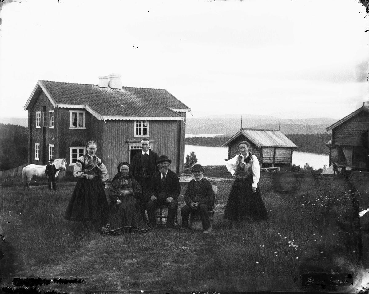 Gruppeportrett med folkedrakt på gårdstun iTelemark antakelig. Hovedhus og satbbur i bakgrunnen.