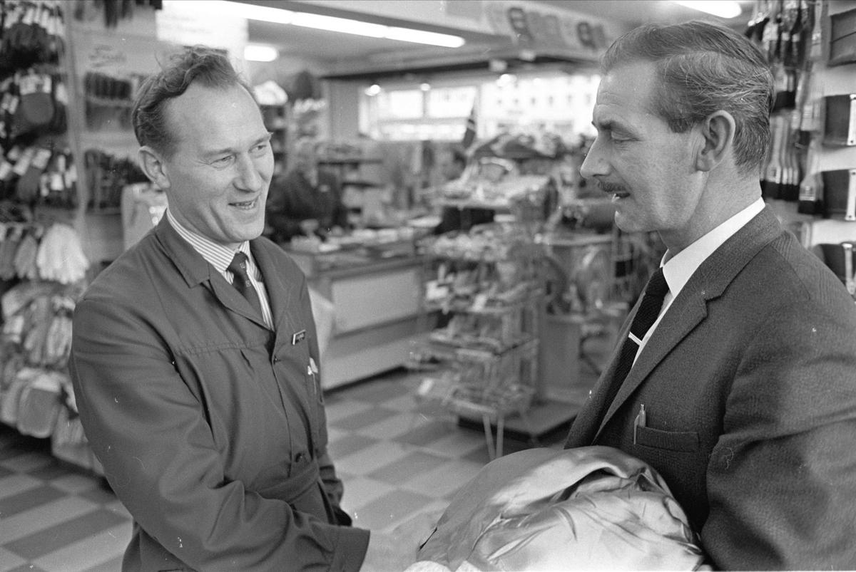Antatt Glomfjord, Meløy, oktober 1965. Artikkel om mann fra Glomfjord-raidet, John Fairclough. Menn hilser i butikk.