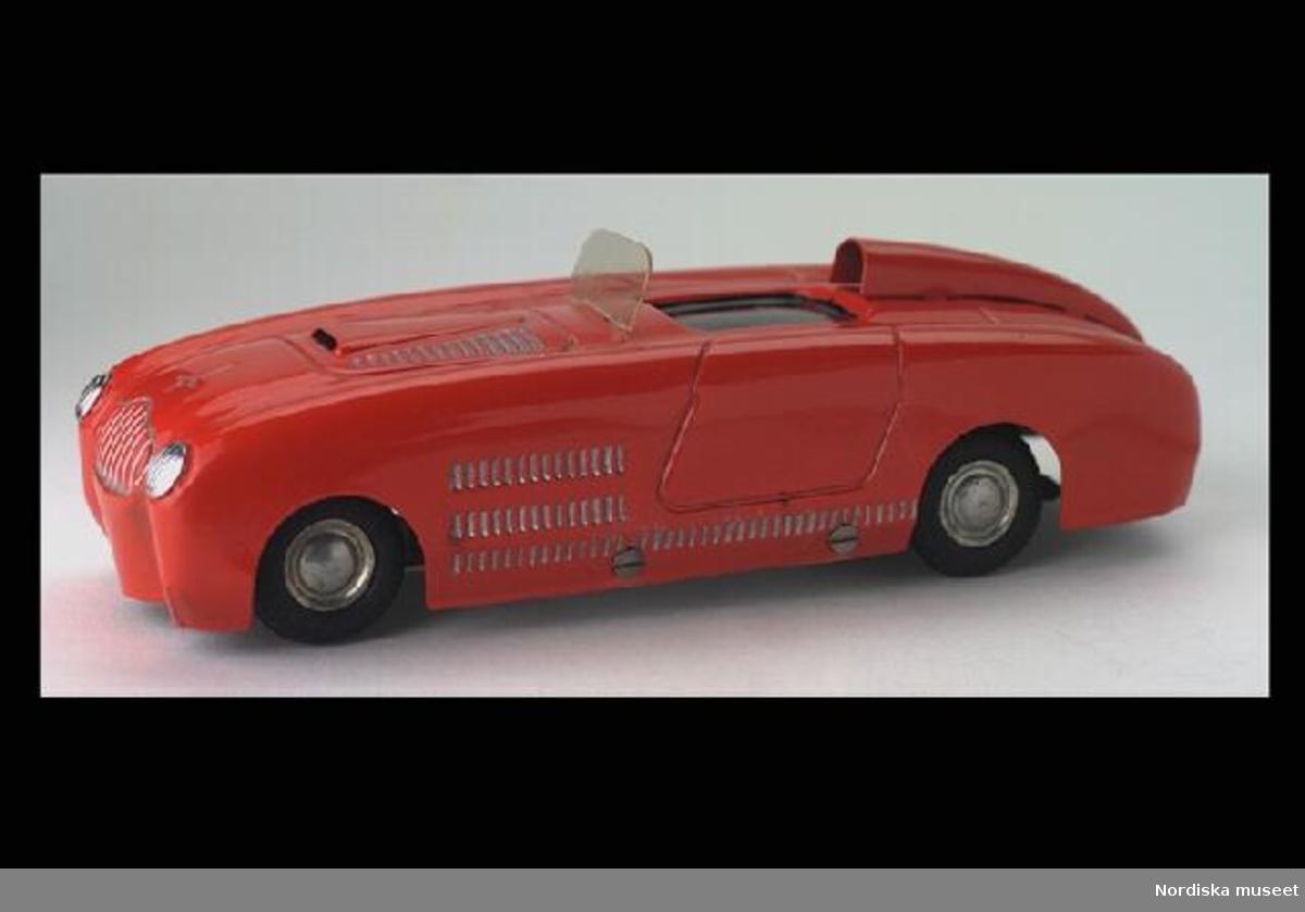 """Inventering Sesam 1996-1999: L 13,5,B 4,7,H 4,5cm Öppen sportbil av modellen Veritas racer modellår 1949, tillverkad av plåt, rödlackerad med silverfärgsmålade detaljer, svart målad förarplats och vindruta av genomskinlig plast. Svarta gummidäck, fjäderverk med stopp- och startspak i bak. Präglad märkning undertill: """"DUX/VERITAS"""". Inköpt för 8,50 kr 1951 på PUB, Stockholm. Givaren samlare av leksaksbilar 1947-1952, se inv 263.905 - 264.120. Bilaga Helena Carlsson 1996"""