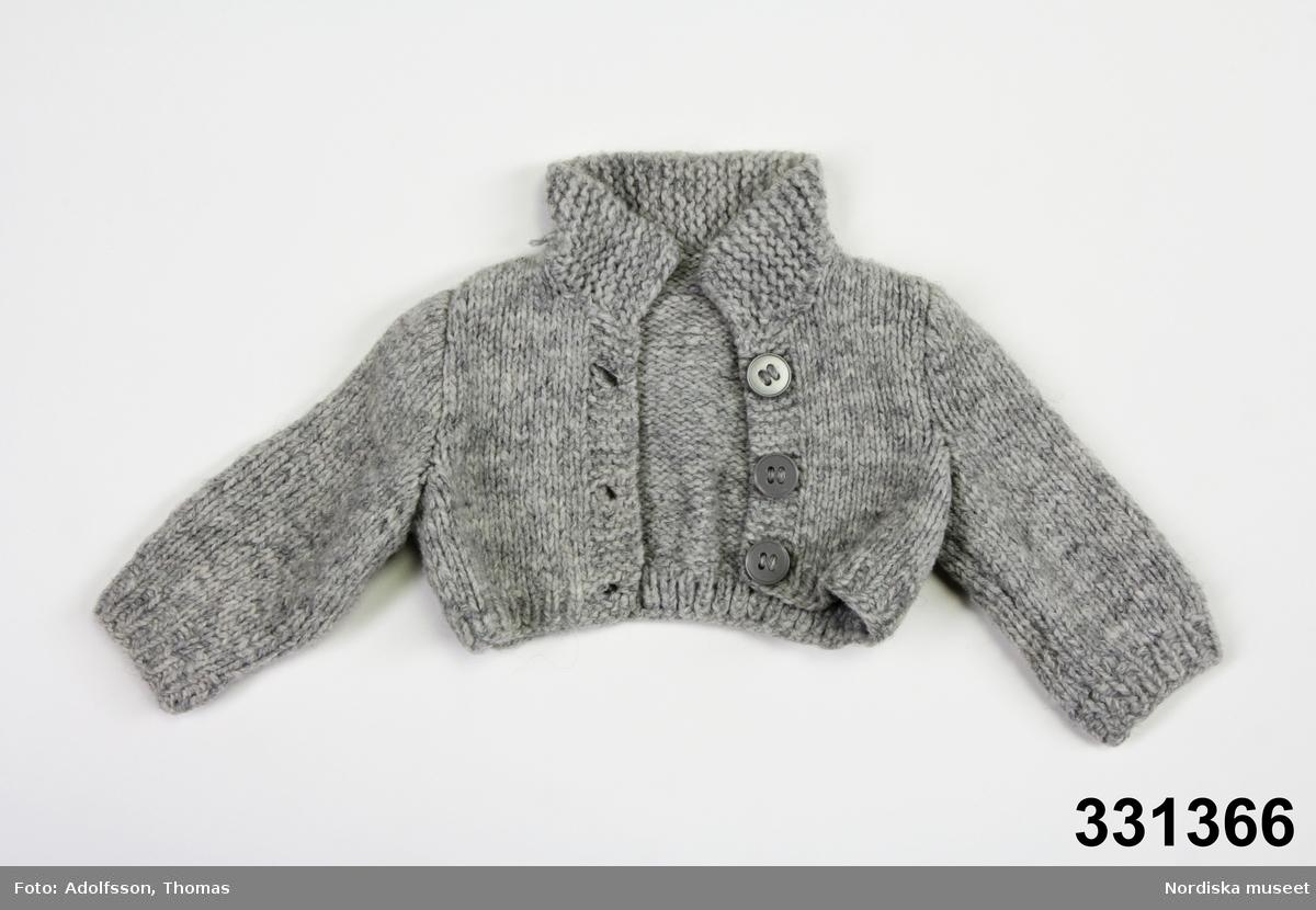 Dockkofta stickad av grått ullgarn med hög krage och knäppning fram med tre plastknappar.  /Karin Dern 2011-09-13