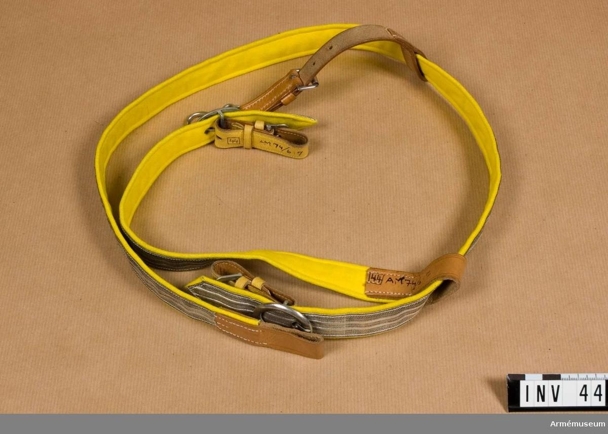 Silvergalon fodrad med gult kläde. Försilvrade söljor och beslag. Två st sabelbärremmar, en i enbart läder. Knäppanordning av gulmålat läder. Har tillhört Gustav VI Adolf (1882-1973).