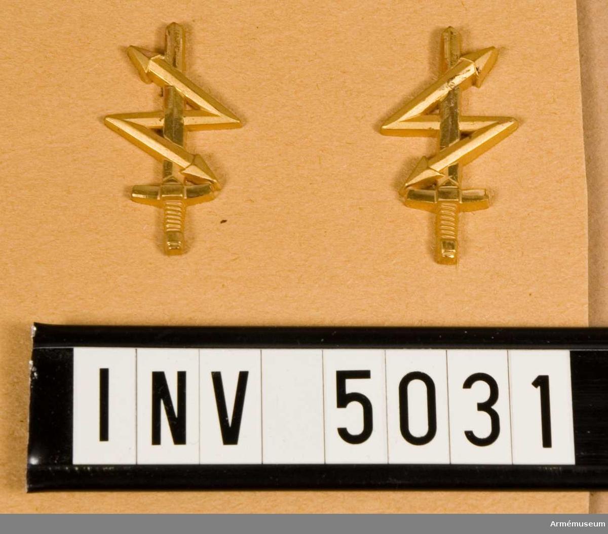 Tillverkat av metall och i metallfärg m/1960 guld. Modellen har  behållits oförändrad från m/1939.Ett upprättstående svärd med blixt. Tillverkas i två storlekar samt spegelvänt.  Det större anbringas på krage till vapenrock och kappa m/1960 samt jacka m/1968 så att blixtens nedersta  spets pekar inåt. Anbringas på ett underlag av grönt tyg i form  av kragspegel.  År 1951 bestämdes att denna färg skulle vara  signaltruppernas färg. Det mindre tecknet anbringas på  axelklaffar till vapenrock och kappa m/1960, jacka m/1968 samt respektive skjortor så att blixtens nedresta spets pekar  framåt.  Detta tecken utan tygunderlag.Anläggs av fast anställd personal som ej tillhör visst förband men personalkåren.