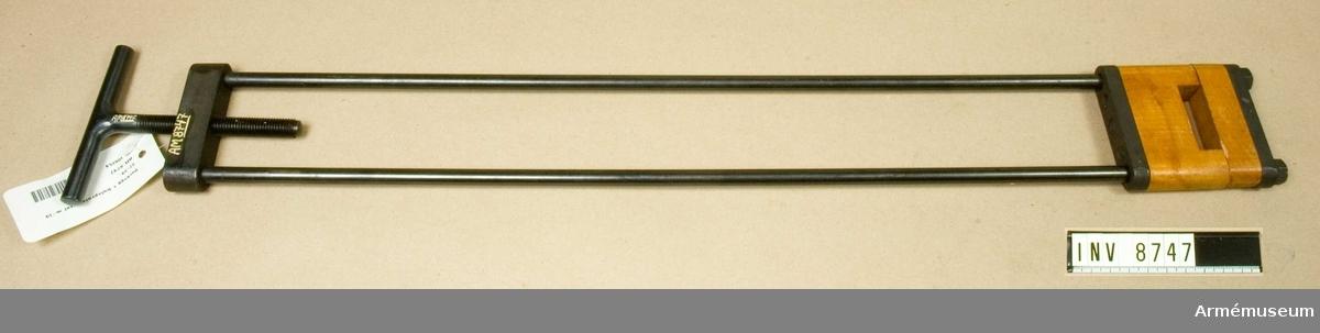 För kolv, montering, består av två rundskenor, två vågformiga, förstärkta backar med tryckklossar av trä, T-handtag av järn. Märkt: Husqvarna Vapenfabriks AB.