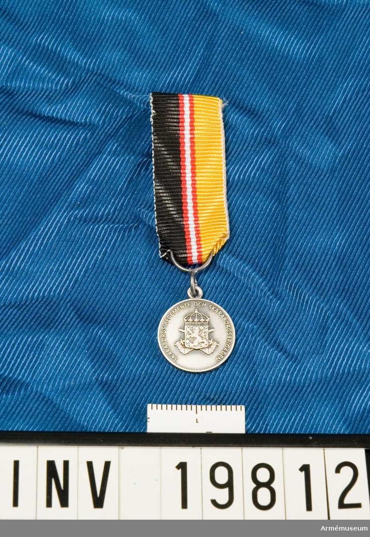 Medaljen är rund. Vapenskölden lagd över två korslagda bepansrade armar hållande varsitt svärd och krönt med en kunglig krona. I skölden ett lejon åtföljt av två stjärnor. På frånsidan en lagerkrans. Inskription: Skaraborgs regemente och Skaraborgsbrigaden. Band kluvet i svart och gult med en vit rand i mitten åtföljd av en röd rand på vardera sidan. Miniatyrmedaljen förvaras i ask tillsammans med en medalj.