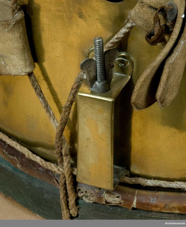"""Grupp C I. Ur uniform för spel, Hälsinge regemente. 1765-79. Består av rock, väst, knäbyxor, hatt, skor, strumpor, strumpeband, halsduk, trumma med rem, trumstockar, livgehäng, huggare. Trumma av mässingsplåt med grönmålad träram. Snörad. Bottenskinnet defekt. Snarrsträngar har funnits men saknas nu. Vingskruvarna för deras  spännande och stället till denna, av mässing, finns dock kvar. """"Trumma för infanteriet från medlet af 1700-talet"""" anger den vidhängande lappen."""