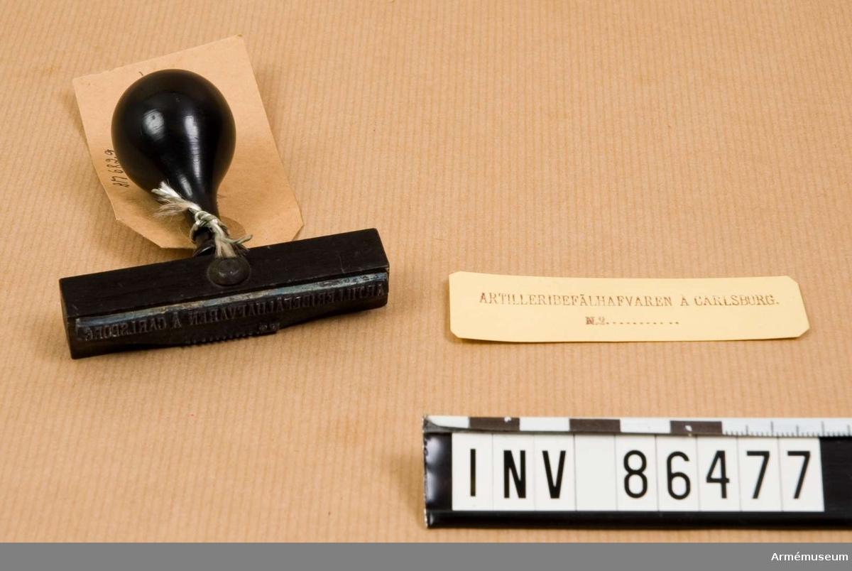 Grupp M V. text på 2 rader. Material: Kartschuk.  Med avtryck på papper.