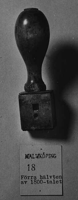 """Datumstämpel, linjär i antikvastil utan ram, texten""""Malmköping 18--"""". Normalstämpel 4 enligt stämpelhandboken, 1952."""
