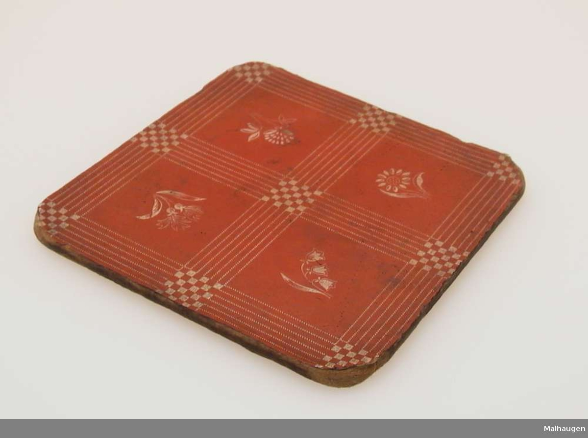 Kjeleunderlag av sponplate med rødt mønstret belegg.