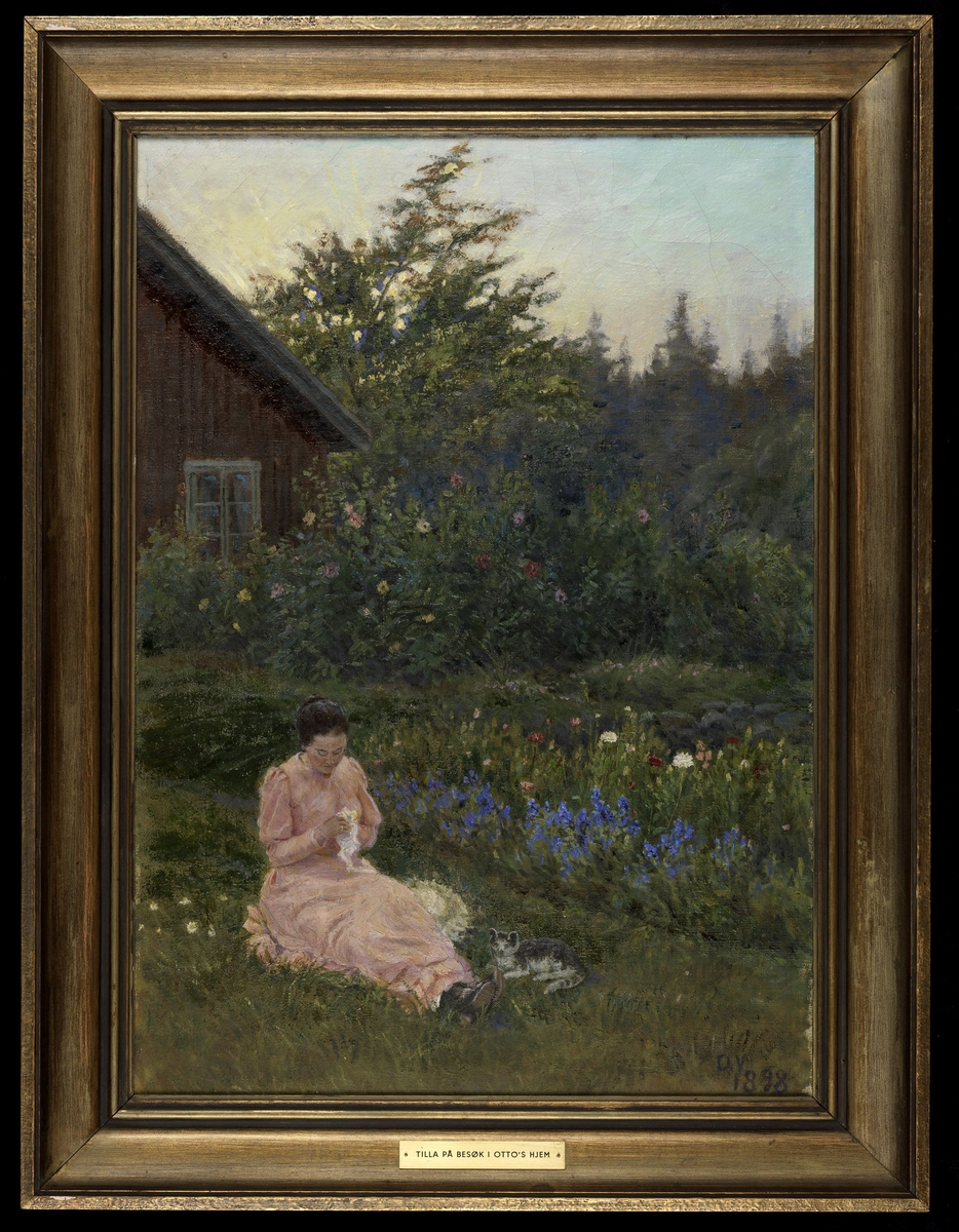 Hage, i forgrunnen Tilla Valstad i rosa kjole sittende i gresset, katt ved siden, blomsterbed, i bakgrunnen hj. av rødt hus, trær.