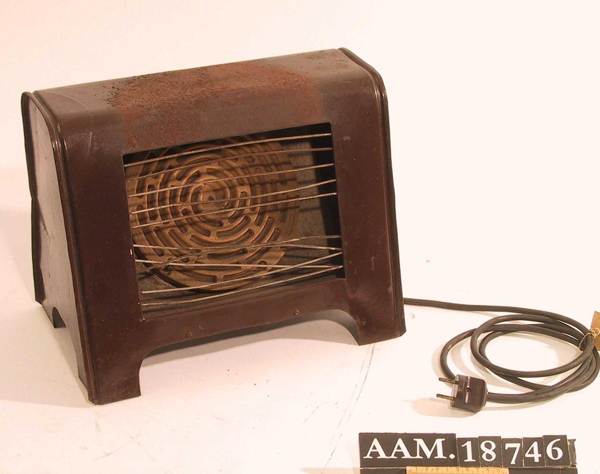Elektrisk ovn fra 1930-årene.   Blikkplater,  malt  mørkebrun, innv. en umalt og med sirkulær plate av lyst gulbrunt   leirtøy,   Stråleovn  med   rektang. åpning med 10 spiler horisontal plassert.  Sort ledning og sort bryter på siden uten tallinndeling. Under innstemplet:   180 - 1200 /220  (= 1200Watt, 220 Volt).  Tilstand: maling avslitt oppå, antag. fordi det har stått kjele med vann der.