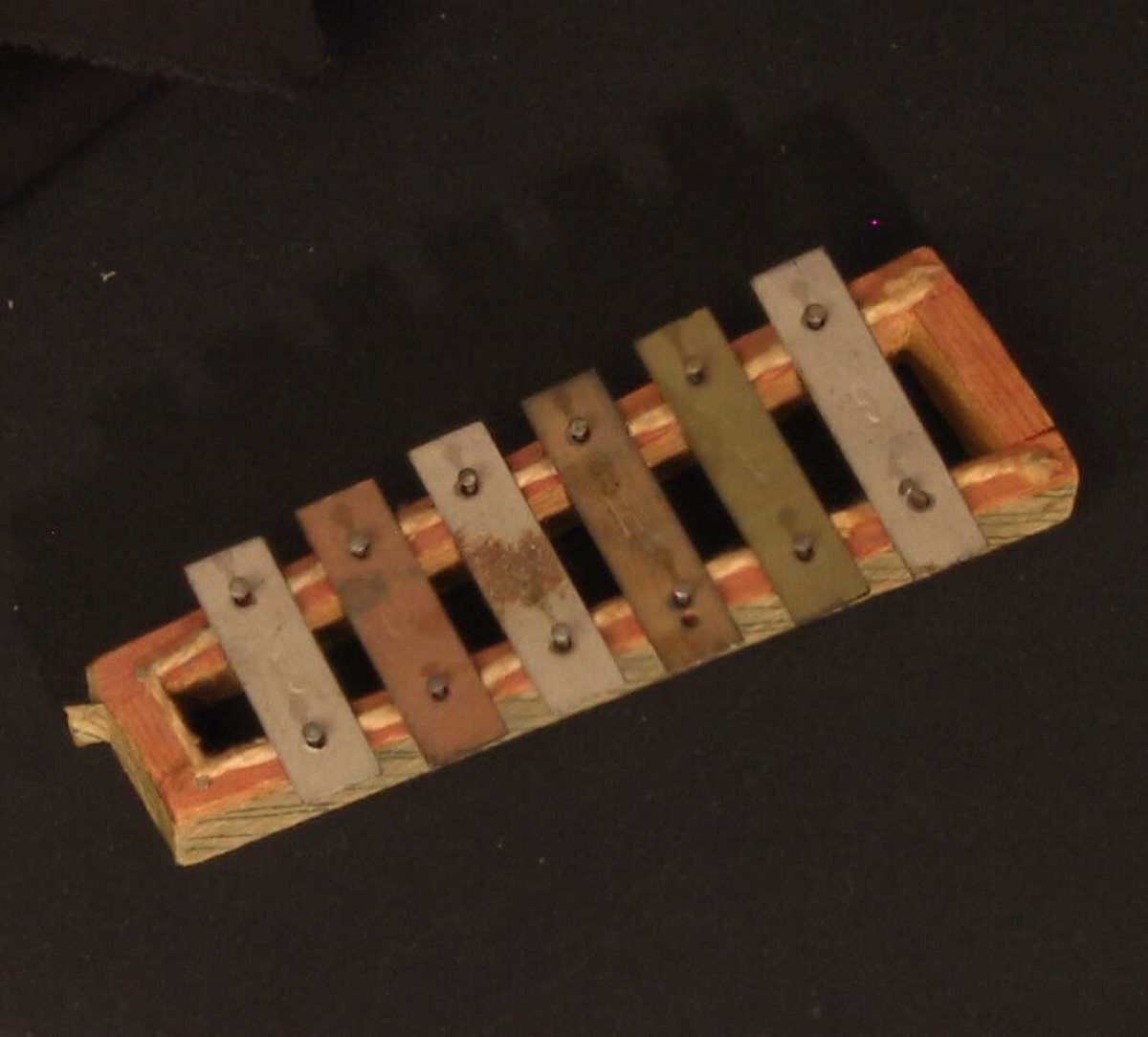 Xylofon, leketøy. Ramme av tre, avsmalnende.   Papir klistra langs kanten.   Metallstykker,  malt av ulik lengde, med trykte bokstaver for tonene, 6 (F mangler)  Under metallstykkene ligger tråd av bomull. Stempla   Tore Barth.  Tilstand mars 1982: Rel. bra.